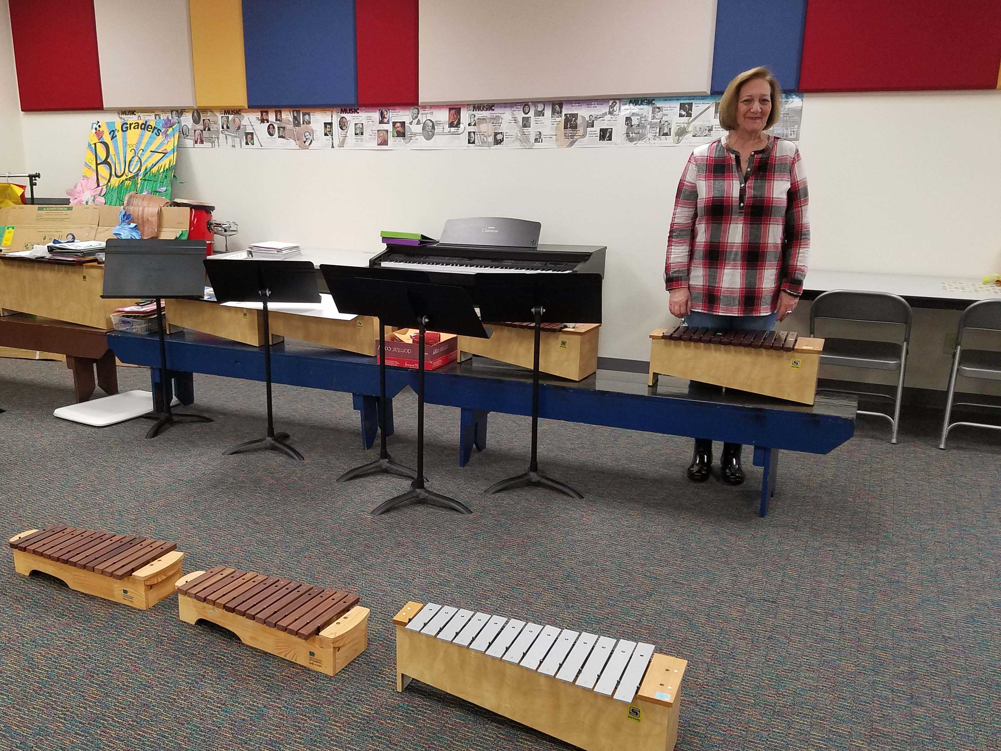 Retiring staff member Debbie Noble stands among some of the instruments she uses to instruct her students at Hart Elementary