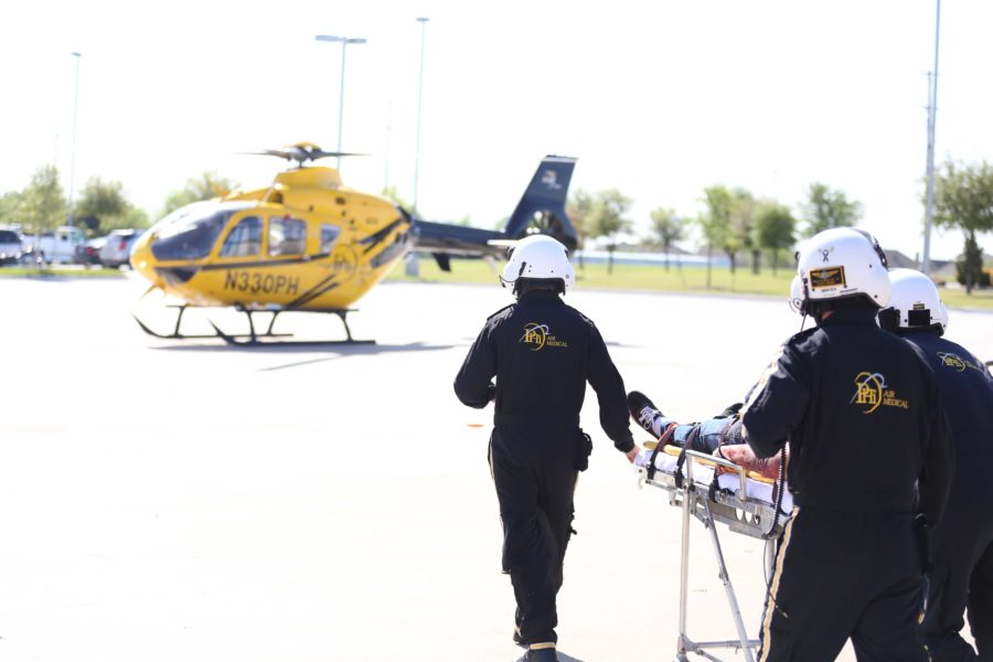 Members of PHI Air Medical, an air ambulance service, rush Andrew Hopkinson to the waiting helicopter.