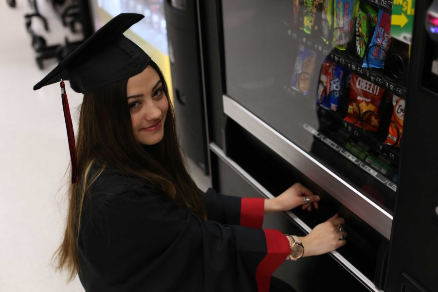 Senior Jordan Toomey, pictured with her beloved vending machine, reflects on her years as a high school student.