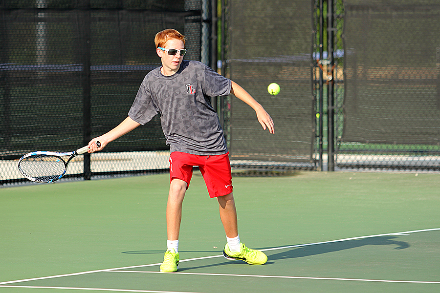 Sophomore Caiden Tays returns a shot for the boys tennis team.