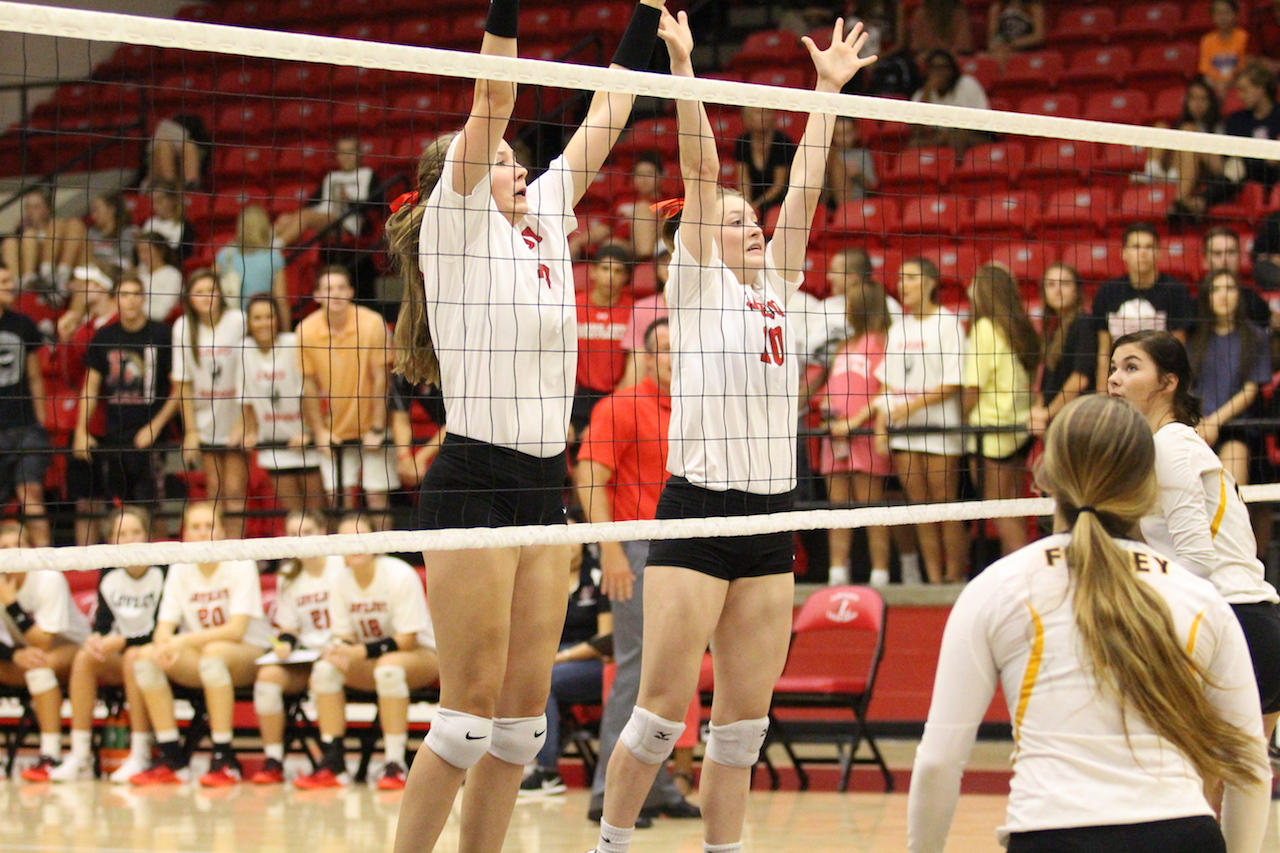 Junior Racheal Langs and sophomore Madison Watters protect the net for their team.