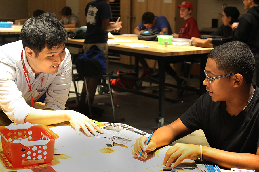 New art teacher Brian Cho helps Art I student Tyrese LaMaison on his drawing. Cho has lived in multiple states and two countries before making his way to Texas.
