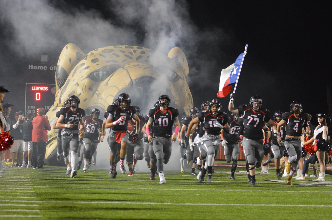 The football team race s out of the Leopard's mouth in front of the FNL crowd.