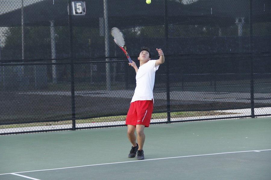 Junior Brandon Su serves to his opponent.