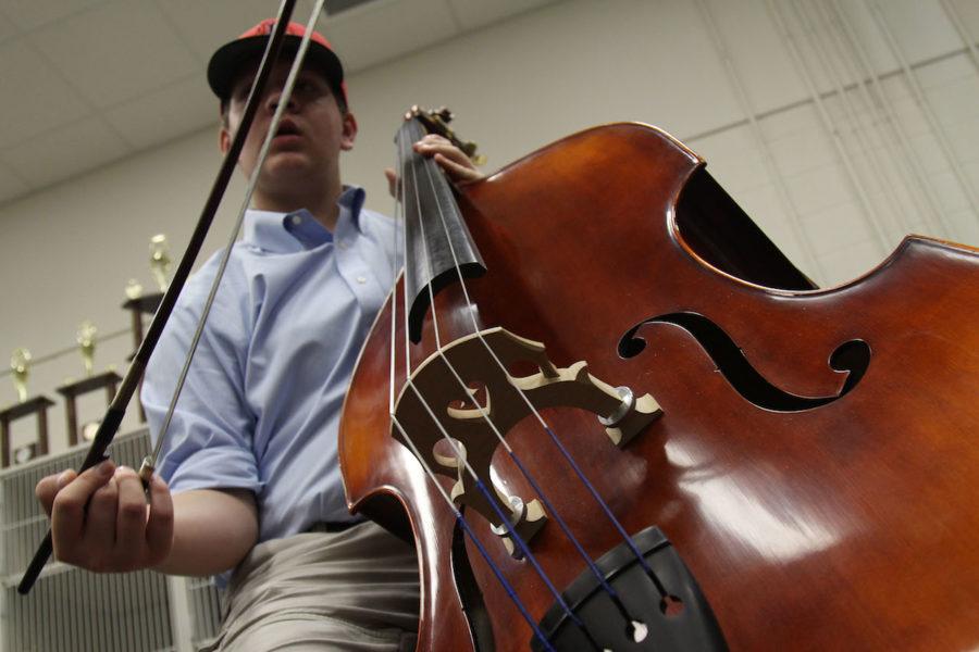 Freshman+Justin+Maroney+holds+his+instrument+