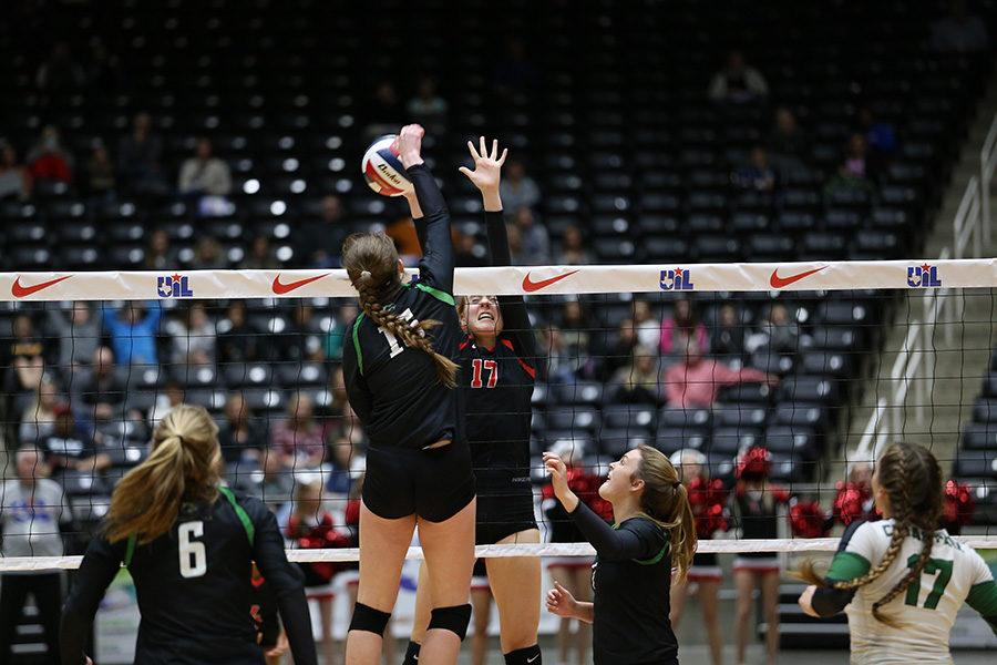 Junior Allie Moger jumps above net to block her opponent's spike.
