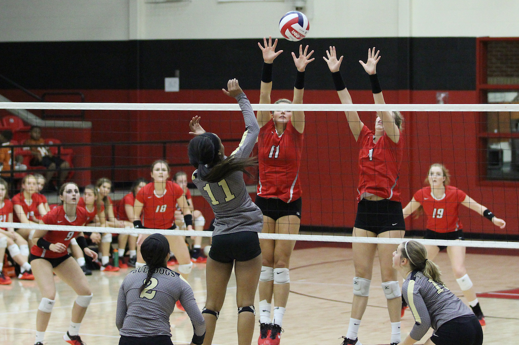Seniors Bailey Downing and Callie Holden block Royse City's hit.
