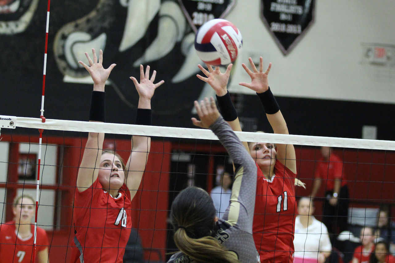 Seniors Paige Becker and Bailey Downing block Royse City's hit.