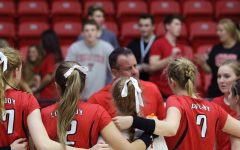 The varsity squad listens to Coach Nicholson during the timeout.