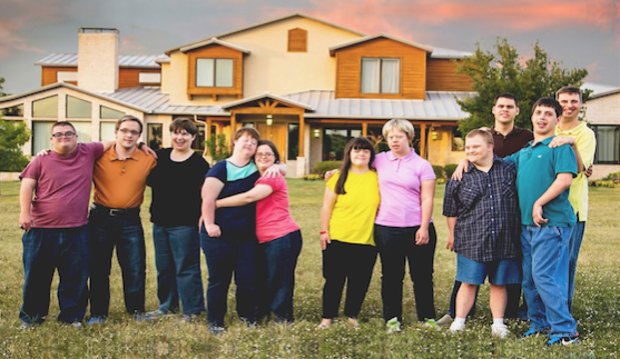 Residents of the Cornerstone Ranch housing program pose outside of one of the structures. Through the program, the adults sell jewelry, make candles, serve others, and grow vegetables among other activities.