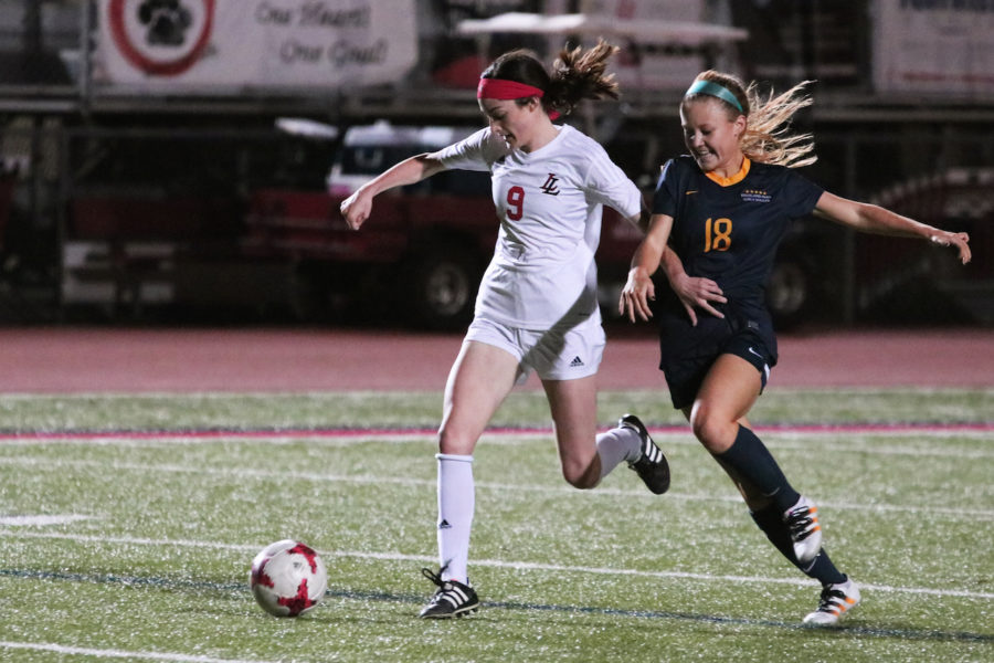 Sophomore Kassidy Litchenburg runs down the pitch with the ball.
