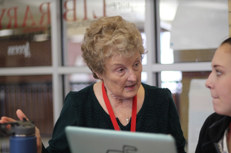 Janet Tillman assists senior Pierce Goddard in connecting her computer to the Wi-Fi in the library.