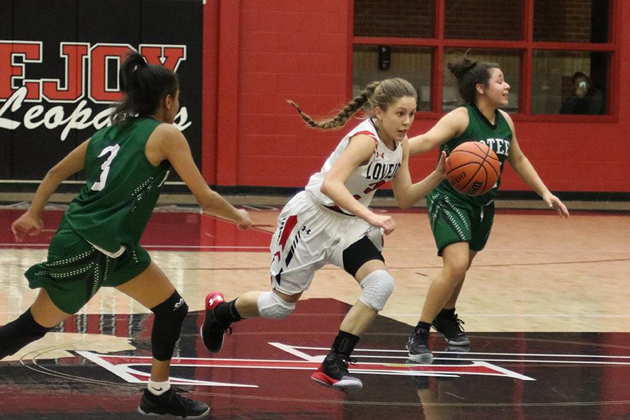 Junior Meredith Ehlman dribbles past Poteet defenders on Jan. 10.