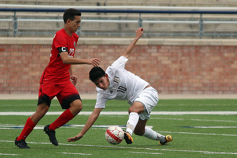 Junior Enrique Vega tries to slip past a Colleyville Heritage defender at Eagle Stadium on Thursday. The Leopards tied Heritage 1-1 in the season opener.