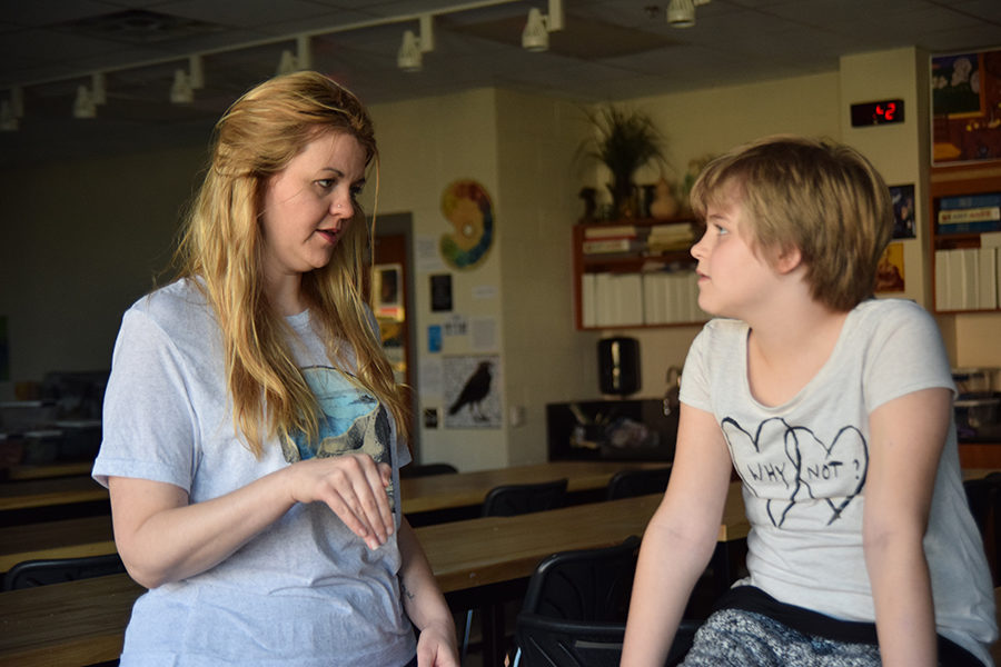 Art teacher Amanda Beller talks with her daughter, Lane, during eighth period. Amanda and her husband, Justin, said they have been intentional about providing their children first-hand experiences with social justice issues.