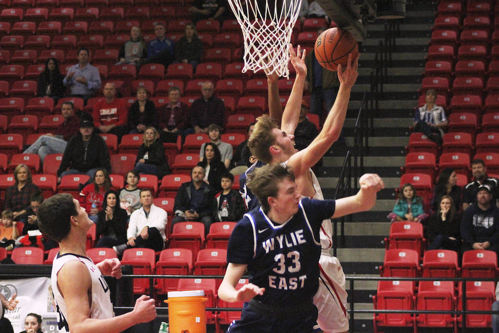 Sophomore Kyle Olson jumps for a lay up while fighting off two Wylie East Defenders.