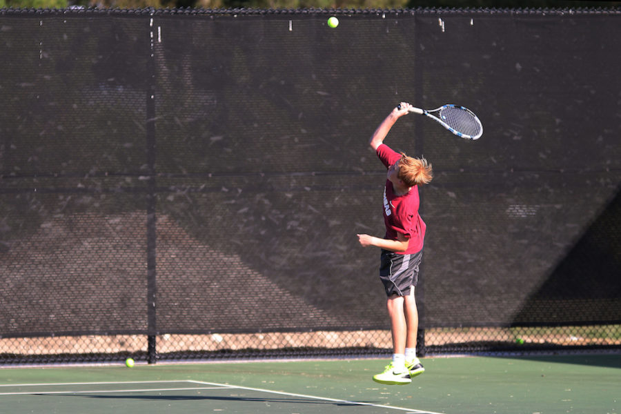Sophomore Caiden Tays jumps to hit ball across the court.
