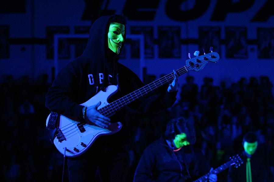 Senior Zach McCormick plays bass during the blacklight pep rally in the gym on March 3.