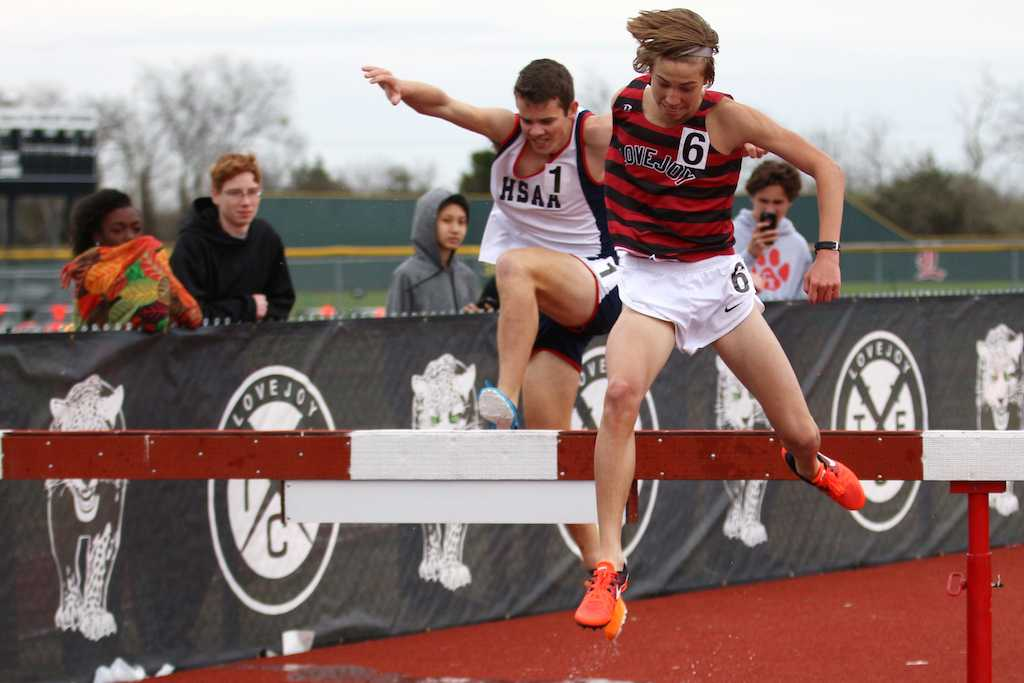 Freshman Whitson Bedel jumping over the steeple chase barrier.