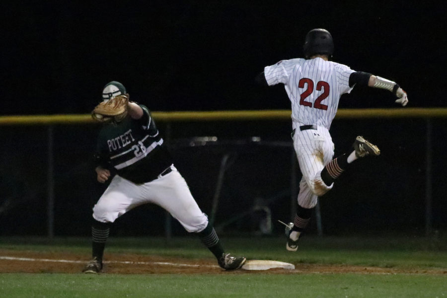 Senior Will Nopper races in an attempt to beat out the throw to first base.