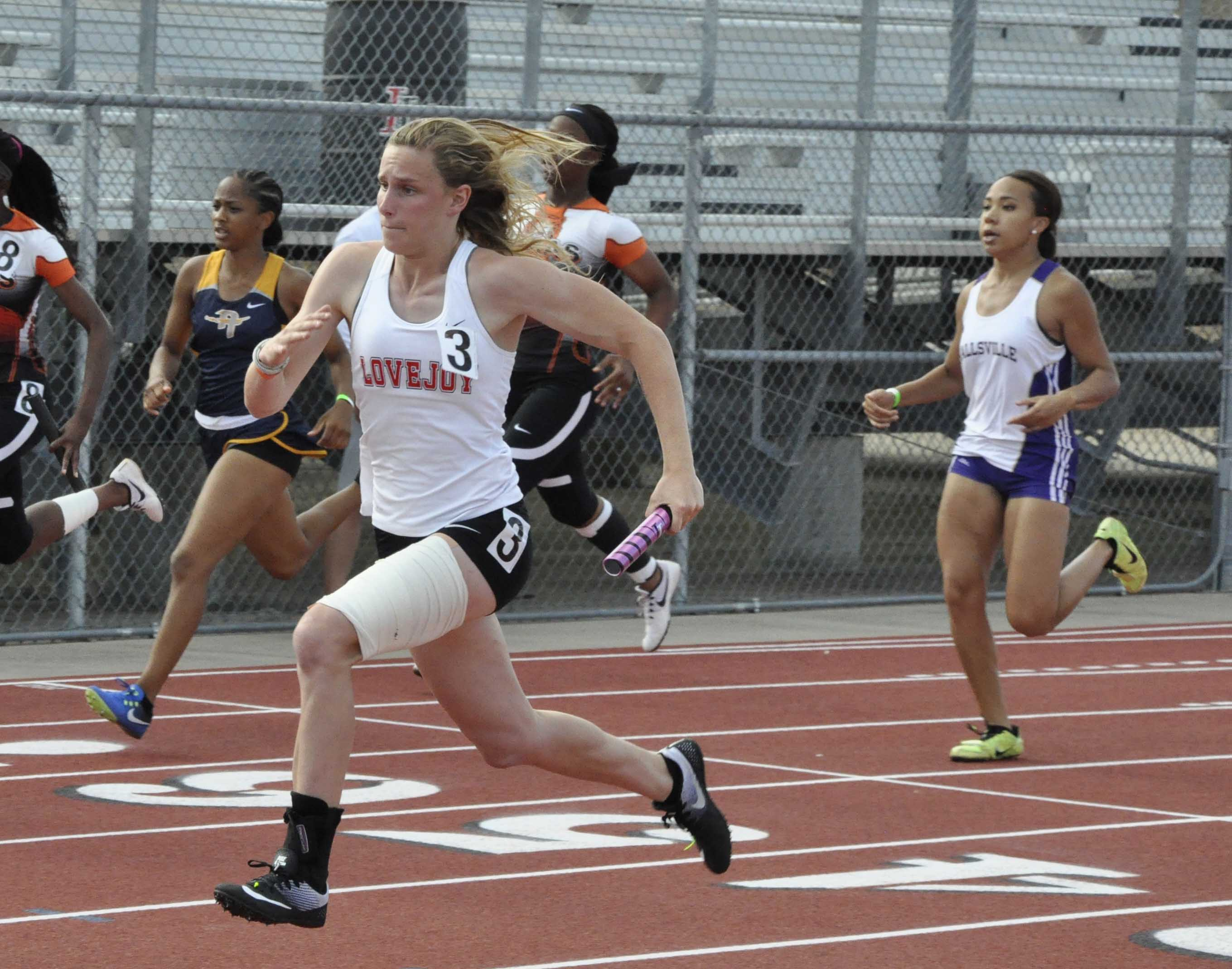 Junior Grace Ridgeway sprints ahead of her competitors in the 4x100 relay. The 4x100 girls team advanced to regionals.