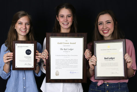 Seniors and editors-in-chief Jillian Sanders, Hallie Fischer, and Caroline Smith hold up the NSPA Pacemaker Finalist, CSPA Gold Crown, ILPC Gold Star awards.