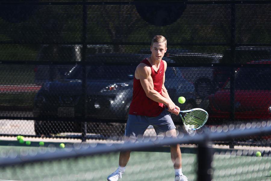 Junior Jack Bennett returns a serve in practice.