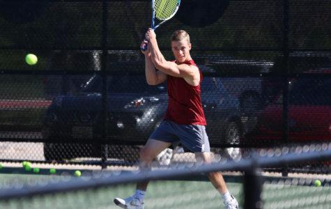 Junior Jack Bennett returns the serve during practice.