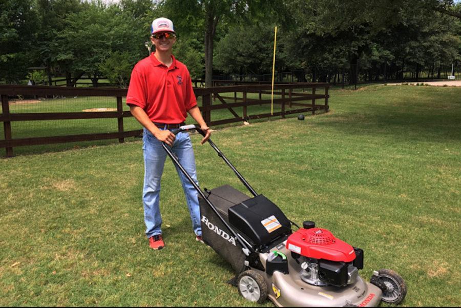 Senior Matthew Almy poses with his money making machine, his lawnmower.