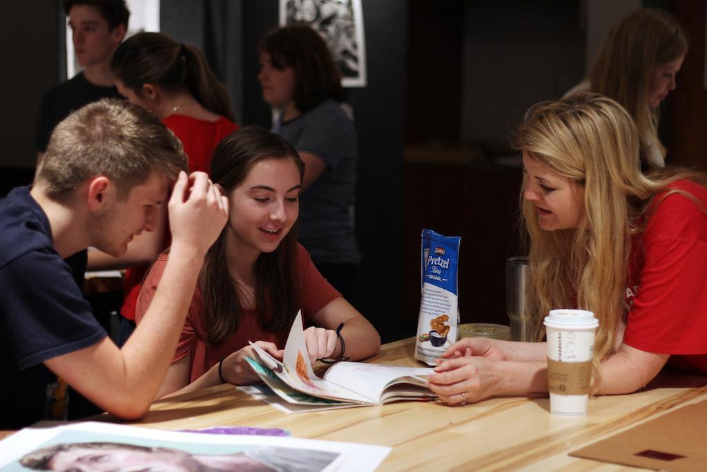 Art teacher Amanda Beller and juniors Emma Wigginton and Elijah Ruhala look over an art piece in the AP art room.