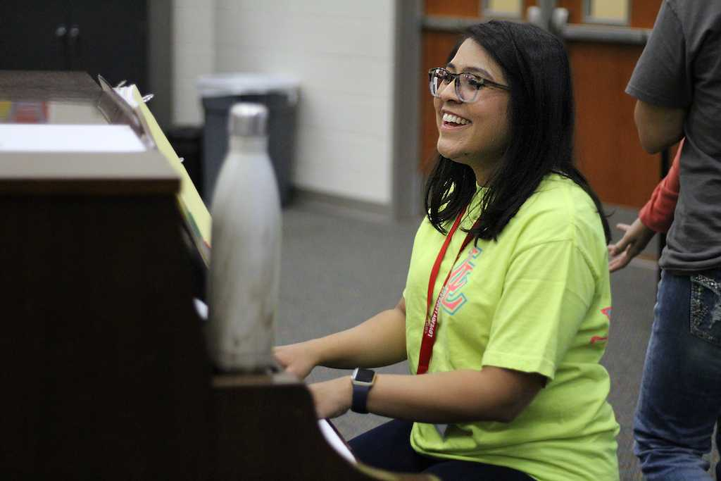 New assistant choir director Kelley D'Souza smiles as she conducts warm ups.
