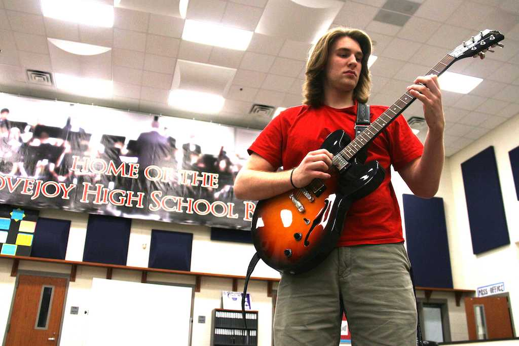 Jack practices on his guitar in the band hall during jazz band rehearsal.