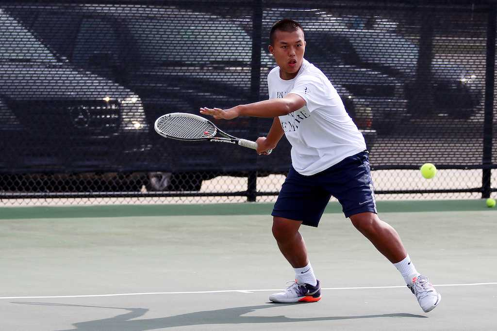 Senior Christopher Sun practices on the tennis court.