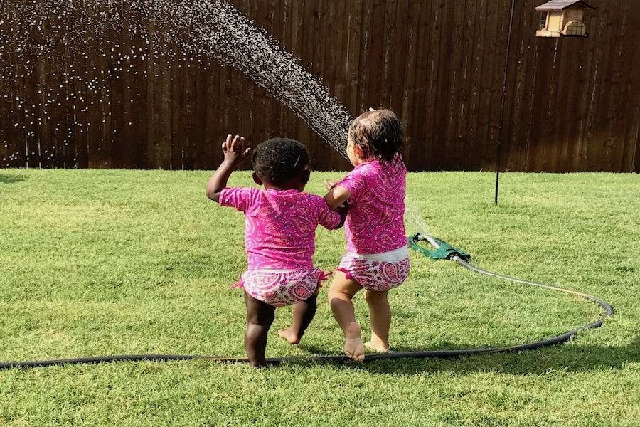 Faith Olsen and the child being adopted play in a sprinkler.