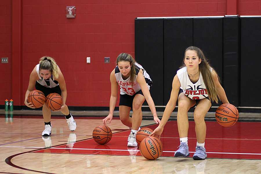 [From left to right] Junior Casey Perkins and sophomores Grace Bennett and Mallory Adamson work on their dribbling in practice.