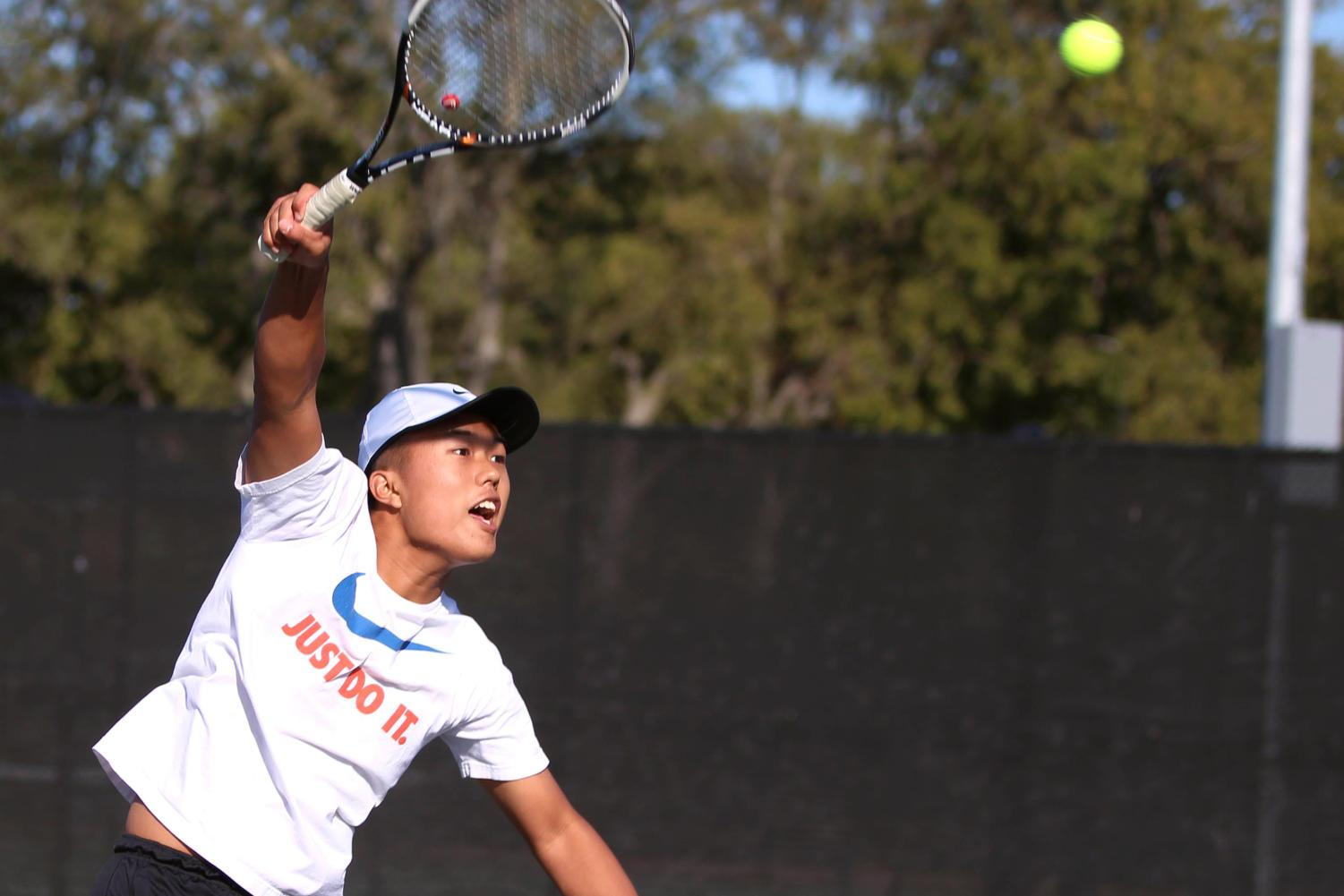 Senior Chris Sun serves the ball during practice.