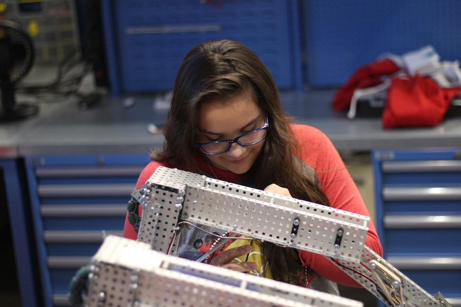 Freshman Madilyn Calderon tinkers with her robot in class.