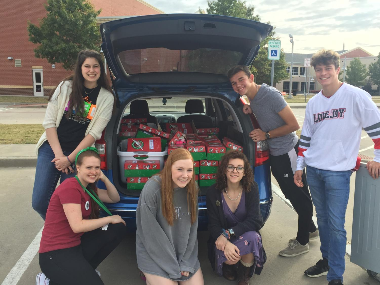 Senior Mandy Rickett, second to the left, and friends who helped pack the boxes packed the gifts in the car to bring them to Operation Christmas Child headquarters. From there they will be given to children in need of christmas gifts.