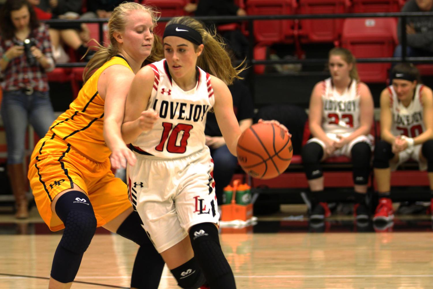 Senior Kaylee Rekieta drives the ball up the floor with pressure from the Highland Park guard.