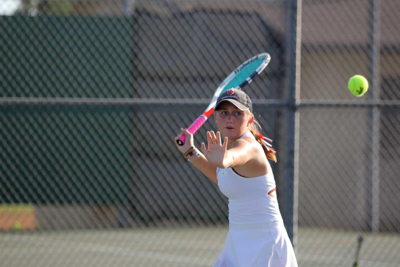 Senior Samantha Hayward aims to return a serve during practice.