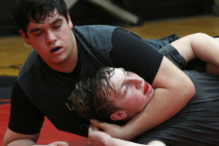 Sophomore Grant Sessions puts freshman Garrison Alling in a headlock during practice on Wednesday.