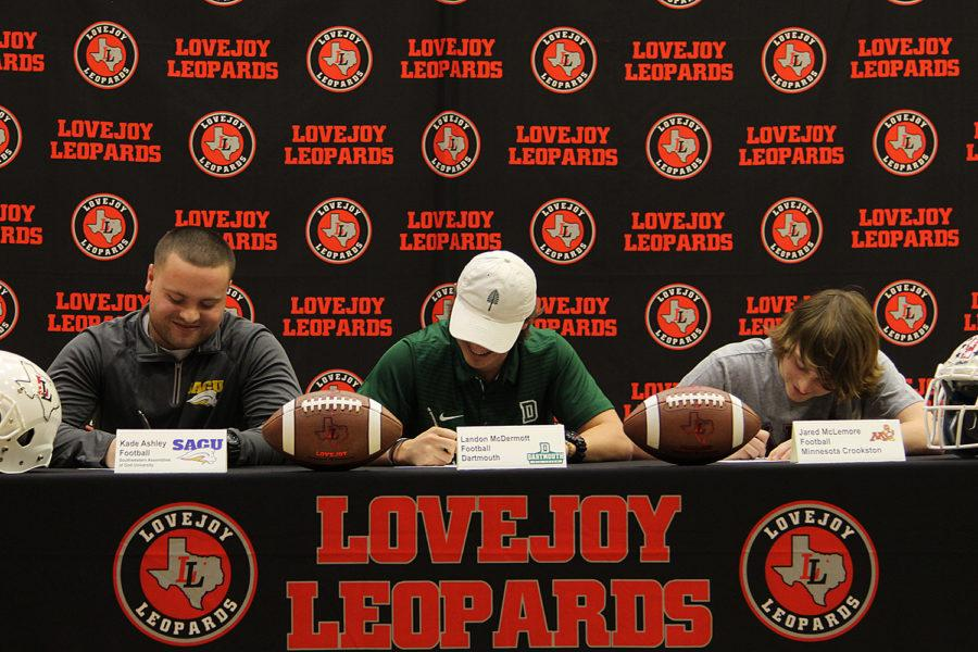The athletes sign their commitments.