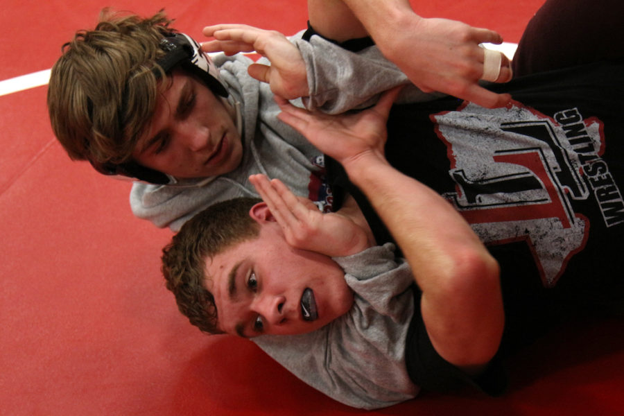 Junior Hunter Duncan puts senior Johnny Dorlon in a head lock during practice.