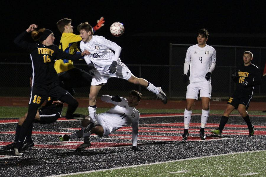 Sophomore Alan Beaney jumps into defender from Forney.
