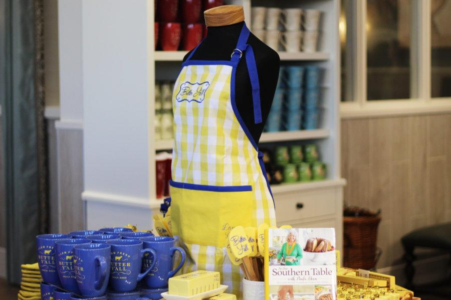 Merchandise+from+Paula+Deen%27s+Family+Kitchen+includes+aprons%2C+mugs%2C+spatulas%2C+and+her+recipe+book.
