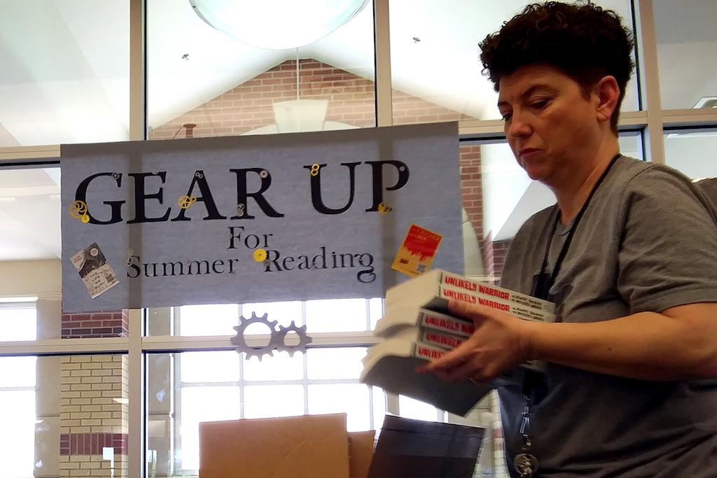 Library media specialist Emma McDonald sets up a book display for the upcoming week.