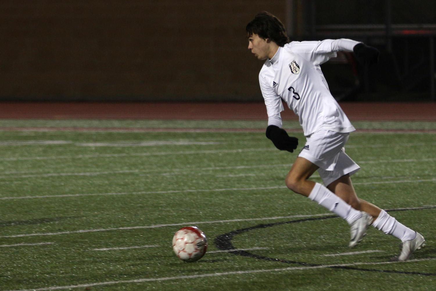Junior Caleb Toomey races up the field with the ball against Forney.