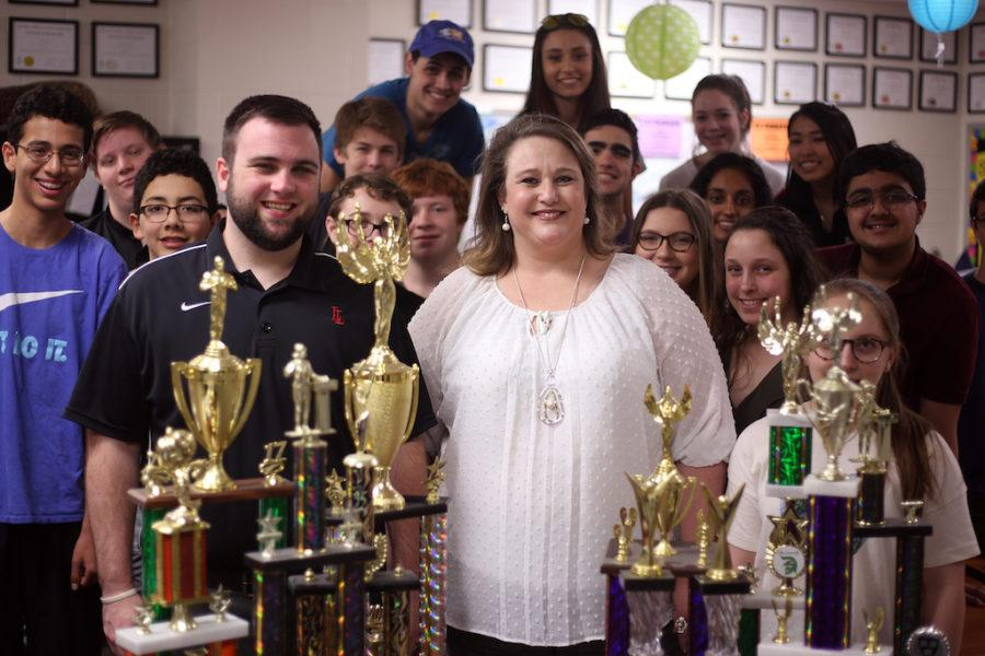 Tami Parker, Jake Cosio and the Debate I students gather around  the Debate team's trophies. Parker will retire in June at the school year's end.