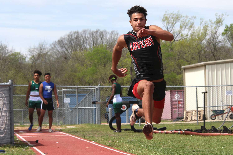 Junior Tyler Van Wagoner propels himself forward during the triple jump.