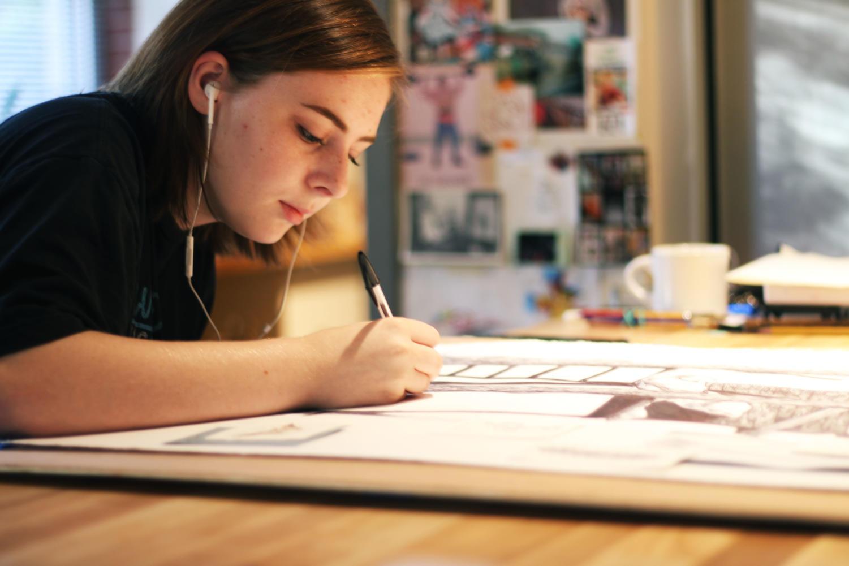 Senior Sarah Nash works with ballpoint pen on her multimedia piece.